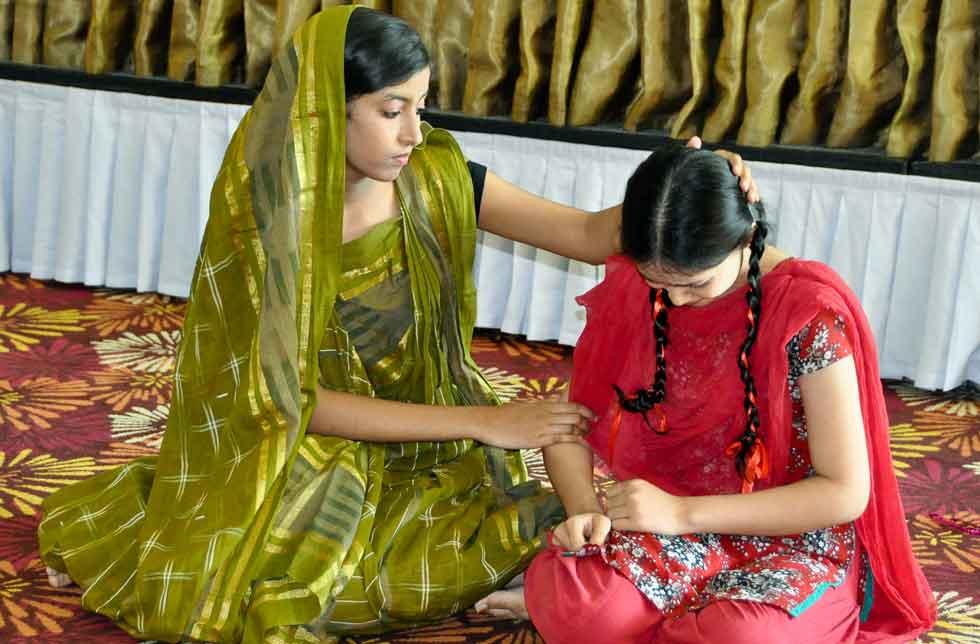 Bangladesch: Ein Mädchen in grünem Sari kniet auf dem Boden und tröstet ein Mädchen in roter Kleidung, das ebenfalls auf dem Boden kniet.