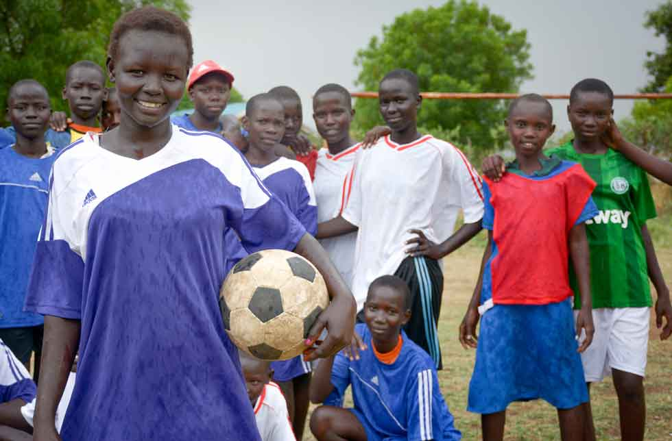 Ein Mädchen in Sportkleidung mit einem Fussball unter dem Arm lächelt in die Kamera, hinter ihr posiert ihre Mannschaft für das Bild.