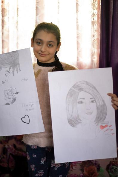 Syrien: Ein Mädchen hält selbstgezeichnete Bilder von Frauen in die Kamera.