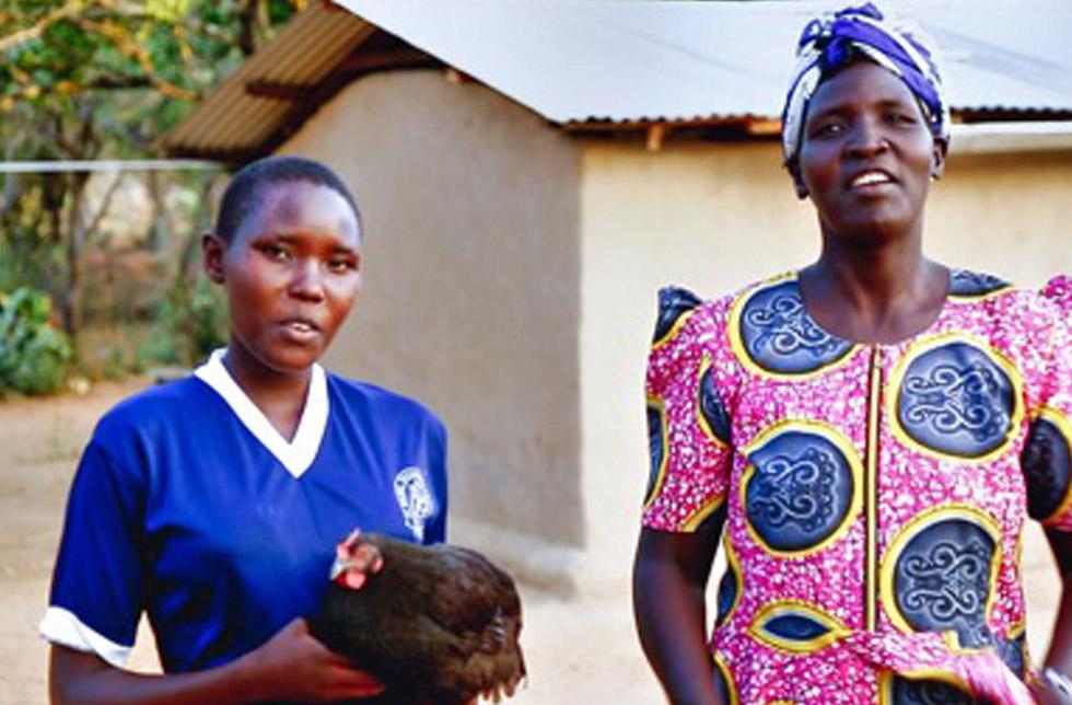 Kenia: Eine Tochter steht mit ihrer Mutter vor einer Hütte.