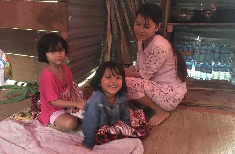 Vietnam: Eine Mutter kümmert sich in einer Notunterkunft um ihre beiden Töchter.