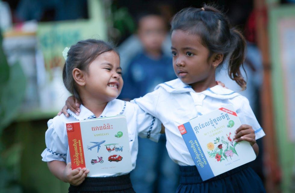 Zwei Mädchen in Kambodscha freuen sich über neue Lehrbücher für die Vorschule.
