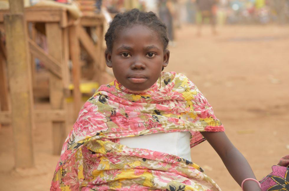 in junges Mädchen aus der Demorkatischen Republik Kongo mit einem geblümten Tuch um die Schultern sitzt auf einem Markt und schaut in die Kamera.