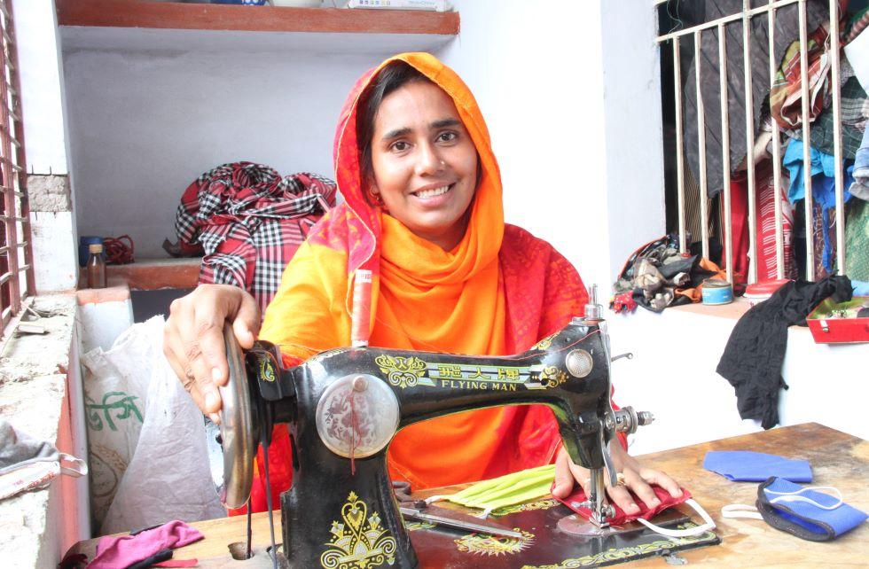 Ein Mädchen aus Bangladesch in einem orangenen Sari sitzt hinter einer Nähmaschine und näht  Mund-Nasenmasken.