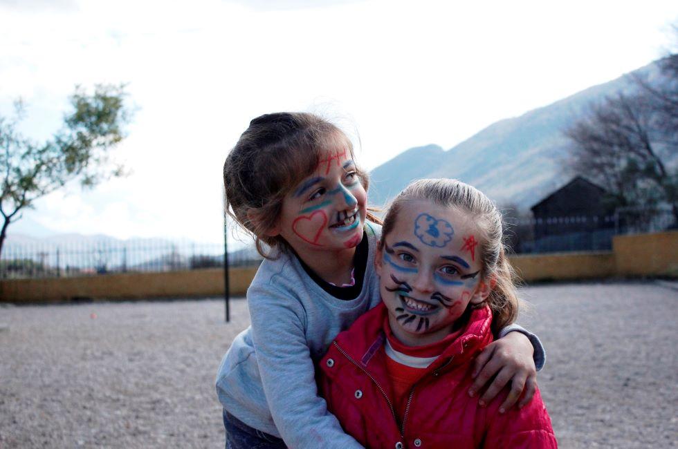 Albanien: Zwei junge Mädchen mit bemalten Gesichtern umarmen sich und lachen