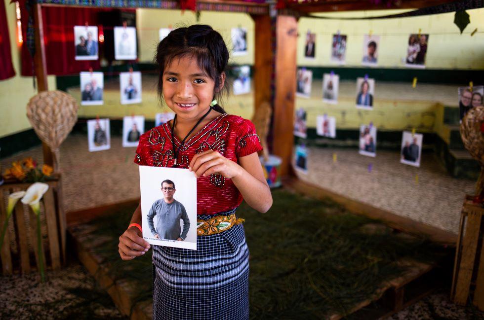 Ein junges achtjähriges Mädchen hält das Foto eines Mannes in der Hand und lächelt in die Kamera
