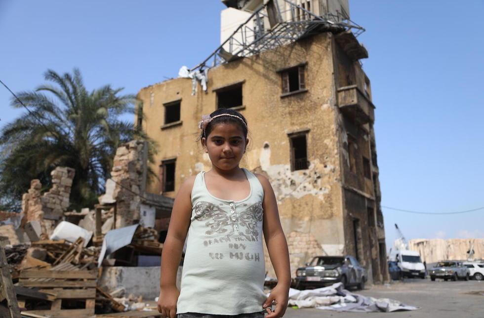 Ein Mädchen steht vor einem zerstörten Haus im Libanon.