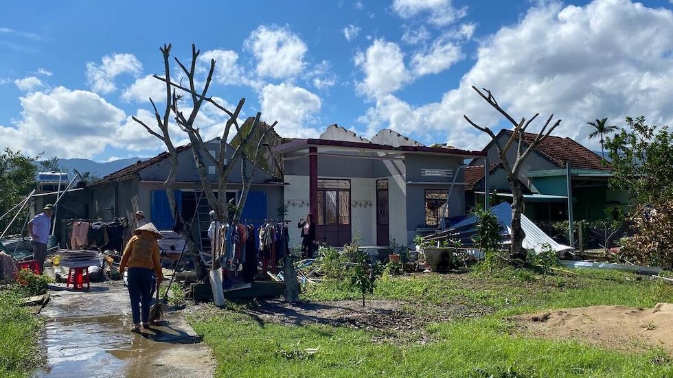 Menschen vor zerstörten Häusern in Vietnam.