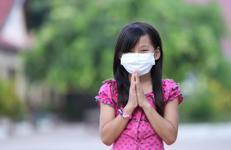 Kambodscha: Ein junges Mädchen trägt einen Mundschutz und hält ihre beiden Hände mit den Handflächen aufeinander zur Begrüssung vor dem Körper.