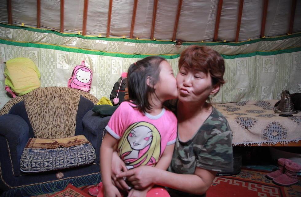 Mongolei: Ein kleines Mädchen sitzt auf dem Schoss einer älteren Frau und gibt ihr einen Kuss auf die Wange.