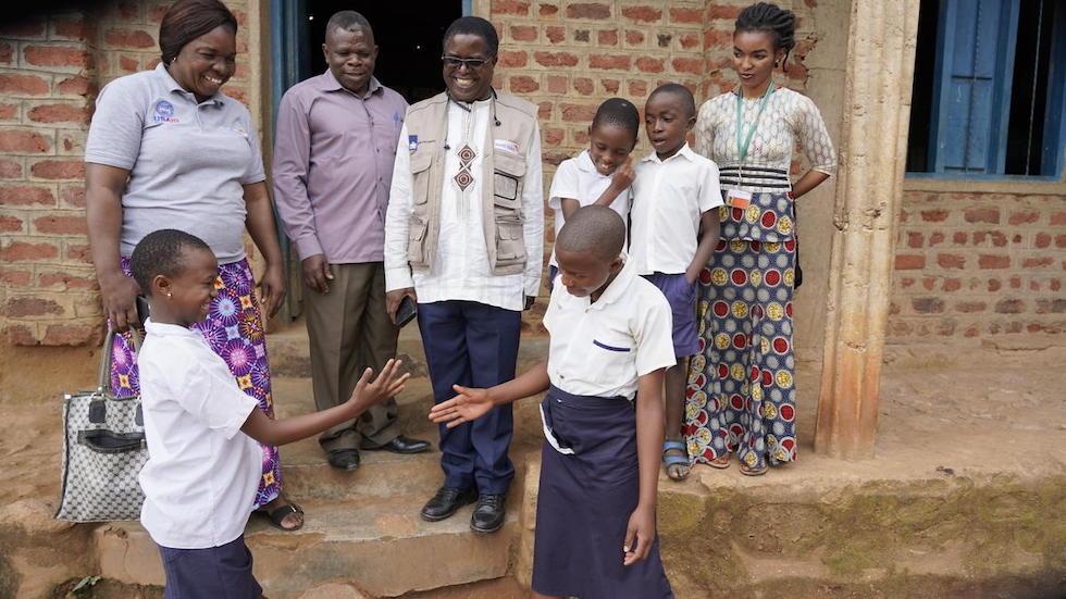 Demokratische Republik Kongo: Zwei Mädchen in Schuluniform geben sich einen Handschlag mit dem Handrücken.
