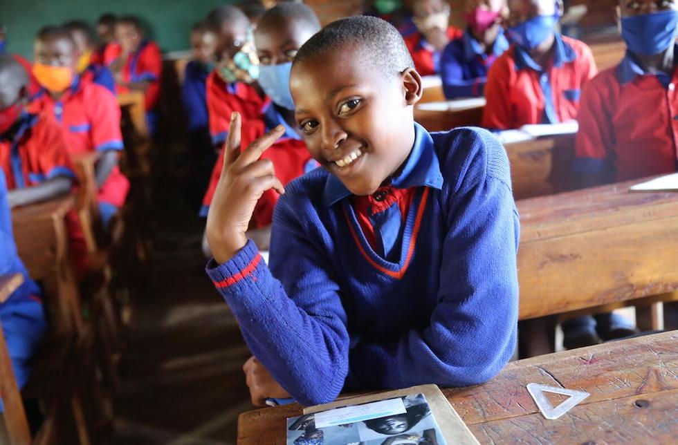 Ruanda: Ein junges Mädchen in Schuluniform sitzt im Klassenzimmer und macht ein Peace-Zeichen mit der Hand. In der Unschärfe hinter ihr sitzen ihre Mitschüler.