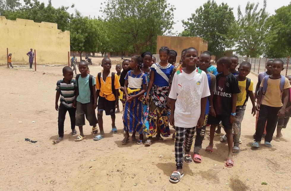 Mali: Eine Gruppe Schulkinder steht auf einem Schulhof und bewegt sich auf die Kamera zu. Hinter ihnen ist ein Zaun zu erkennen.
