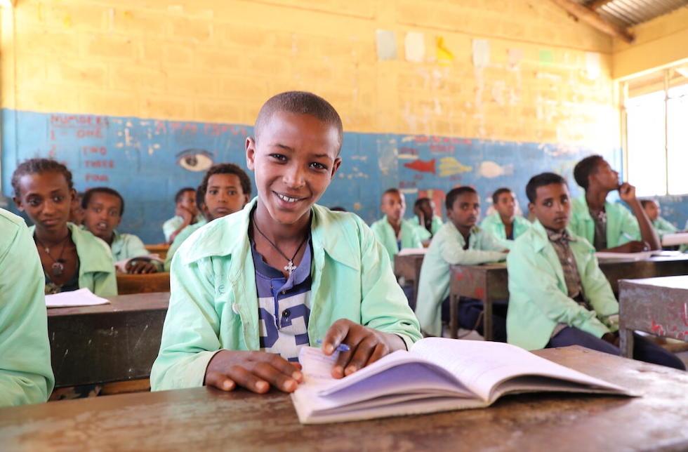 Äthiopien: Ein Junge sitzt in der Schulbank und blättert in einem Buch, das vor ihm liegt. Dabei lächelt er in die Kamera. Im Klassenzimmer hinter ihm sitzen seine Mitschüler.