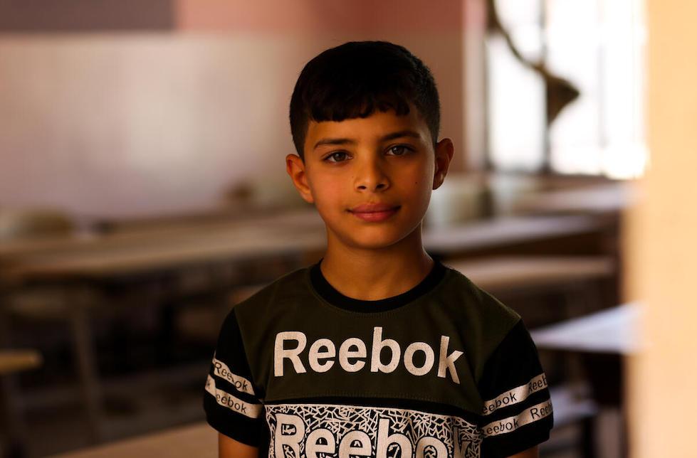Irak: Porträt eines Jungen. Er trägt ein Reebok-Shirt, hinter ihm ist unscharf ein Klassenzimmer zu erkennen.