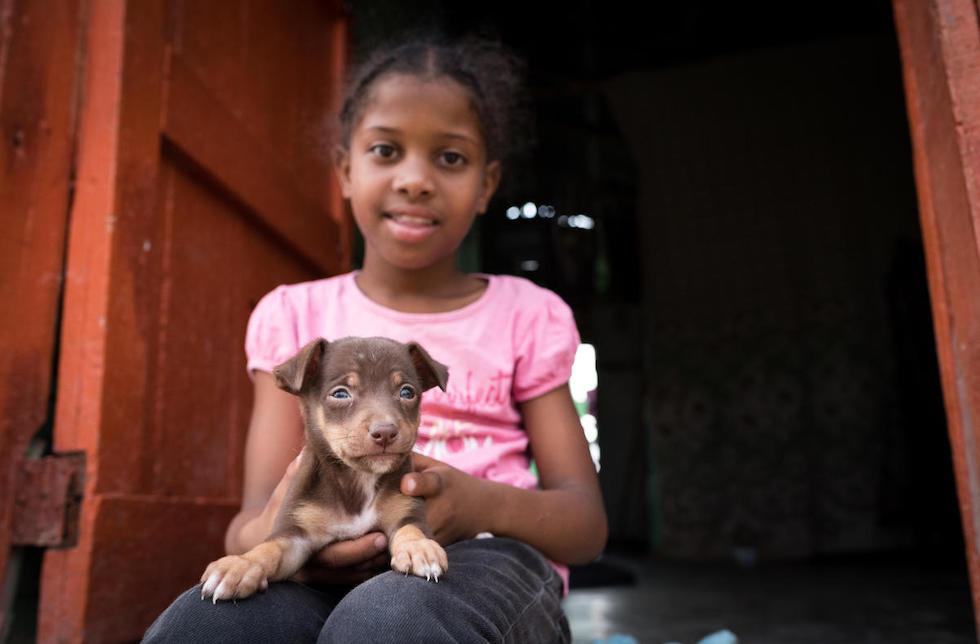 Dominikanischen Republik: Ein junges Mädchen sitzt in der Tür und hat einen kleinen Welpen auf dem Schoss.