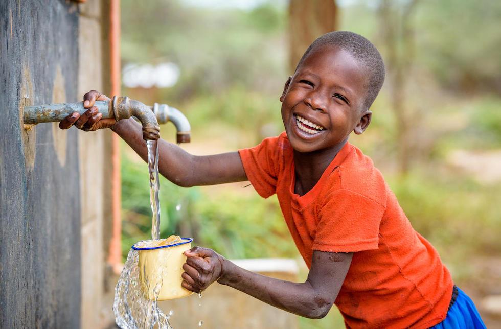Kenia: Ein lachender Junge füllt an einem Wasserhahn seinen Becher mit Wasser auf.