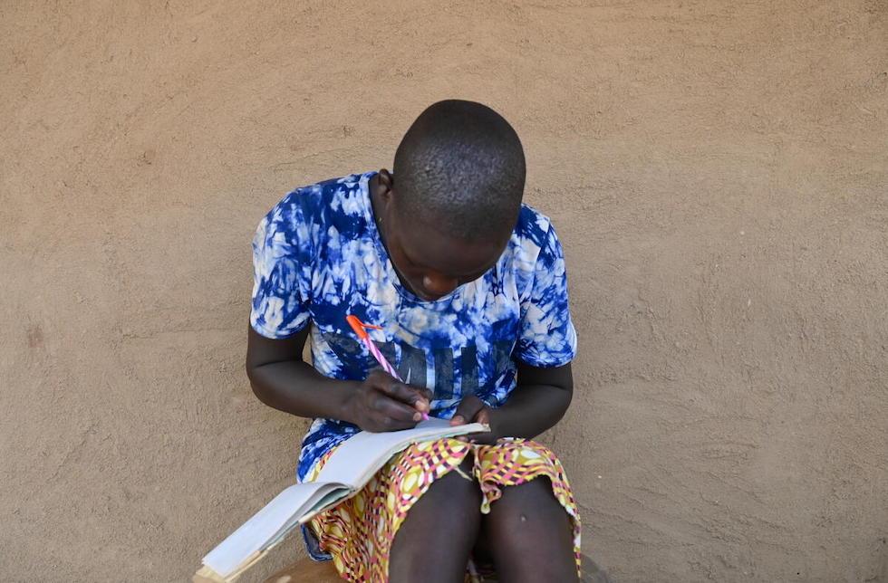 Kenia: Ein junges Mädchen sitzt an einer Wand und schreibt in ein Heft, dass auf ihren Beinen liegt.