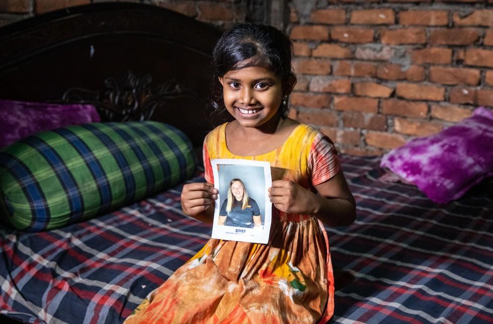 Bangladesch: Ein Mädchen hält stolz das Bild ihrer Patin in der Hand.