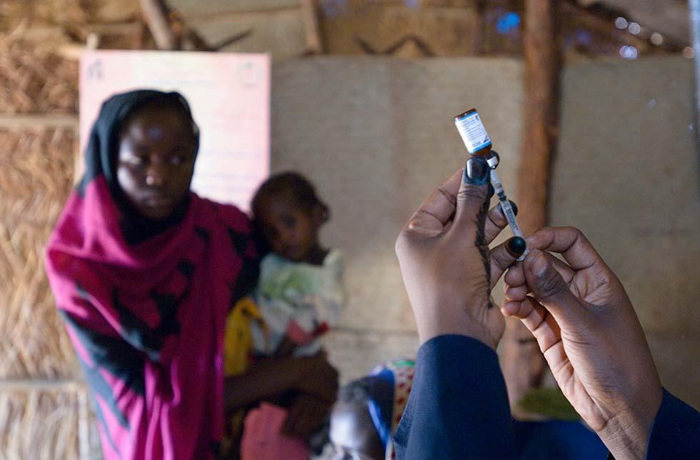 Sudan: Ein Paar Hände hält eine Spritze und Injektionsmittel, eine Mutter mit Kind schaut dabei zu.